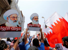 "Protesters holding Bahraini flags and placards with images of Bahrain's leading Shi'ite cleric Isa Qassim, shout religious slogans during an anti-government protest after Friday prayers in the village of Diraz, west of Manama, Bahrain, August 12, 2016. The placards read, ""We sacrifice our souls for you"". REUTERS/Hamad I Mohammed - RTSMVK8"