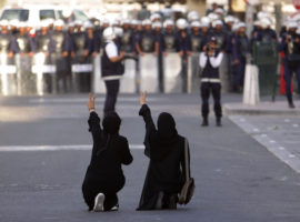 FILE- In this Wednesday, Jan. 18, 2012 file photo, Bahraini anti-government protesters kneel in the street and gesture toward riot police, in Manama, Bahrain. Bahrain's security forces tortured detainees in the years after its 2011 protests despite a government promise to stop such abuses in the island nation, according to a new report released Monday. The Human Rights Watch report on Bahrain, home to the U.S. Navy's 5th Fleet, corresponds with accounts of abuse provided by Amnesty International and local activists.(AP Photo/Hasan Jamali, file)