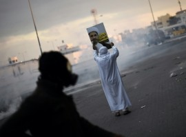 A Bahraini protester holds a placard depicting a portrait of Sheikh Ali Salman, head of the Shiite opposition movement al-Wefaq, during clashes with riot police following a protest against Salman's arrest in the village of Sitra, south of the capital Manama, on January 29, 2016. / AFP / MOHAMMED AL-SHAIKH