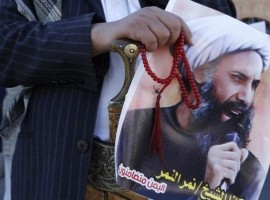 A Shi'ite protester carries a poster of Sheikh Nimr al-Nimr during a demonstration outside the Saudi embassy in Sanaa October 18, 2014. REUTERS/Khaled Abdullah