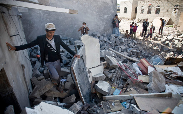 In this Tuesday, March 31, 2015 file photo, people gather near the rubble of houses destroyed by Saudi airstrikes near the airport in Sanaa, Yemen.