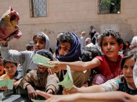 Hungry children in Yemen wait for aid.