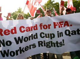 Members of the Swiss UNIA workers union display red cards and shout slogans during a protest in front of the headquarters of soccer's international governing body FIFA in Zurich October 3, 2013. Fifa's executive committee is meeting in Zurich on Thursday and Friday and discussing whether the Qatar 2022 World Cup should be moved from Summer to Winter because of the heat. Qatar has also been hit by criticism of its treatment of migrant workers after a report in the Guardian newspaper said that dozens of migrant Nepalese workers have died in recent weeks. The red cards read 'Red card for FIFA - No World Cup without human rights.'  REUTERS/Arnd Wiegmann (SWITZERLAND - Tags: CIVIL UNREST SPORT SOCCER BUSINESS EMPLOYMENT SOCIETY)